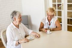 在家喝coffe和谈话的两个老妇人 库存图片