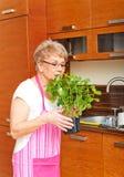 在家嗅到她薄荷的植物的老妇人在厨房里 免版税库存图片