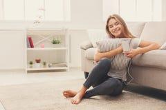 在家在家听到音乐的微笑的女孩 免版税库存图片