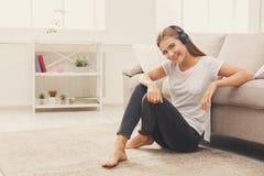 在家在家听到音乐的微笑的女孩 库存照片