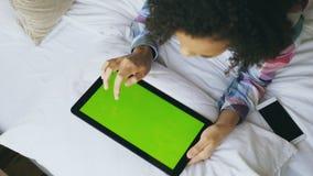 在家在床上的卷曲混合的族种妇女顶视图使用有绿色屏幕的电子片剂 库存图片