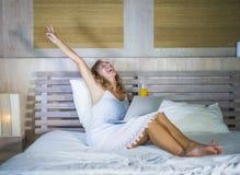 在家在床上的年轻可爱和美丽的愉快的白种人妇女30s使用研究计算机膝上型计算机的互联网微笑关于 免版税库存图片