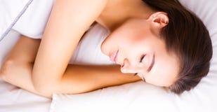 在家在床上的年轻美丽的妇女 免版税库存照片