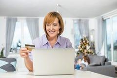 在家在网上购物在圣诞节期间的愉快的妇女 免版税库存图片
