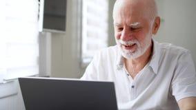 在家坐与膝上型计算机的老人 使用计算机谈话通过信使app 在问候的微笑的挥动的手 股票视频