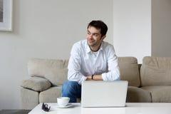 在家坐与膝上型计算机的年轻人 图库摄影