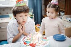 在家坐与蜡烛的兄弟和姐妹蛋糕 免版税库存图片