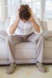 在家坐与头的穿着体面的人在手上 库存图片