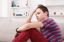 在家坐乏味不快乐的十几岁的男孩 免版税库存图片