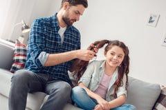 在家坐人的父亲和一点女儿做辫子对女儿被集中 图库摄影