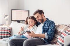 在家坐人陈列女孩新应用的父亲和一点女儿惊奇 库存图片