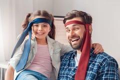 在家坐佩带的领带的父亲和一点女儿笑特写镜头 图库摄影