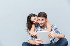 在家坐和使用数字式片剂的夫妇 免版税库存照片