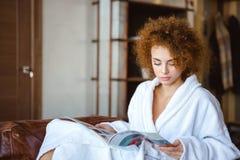 在家坐和读杂志的逗人喜爱的可爱的平静的女性 免版税库存图片