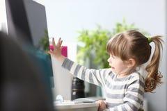 在家坐在与计算机的工作台工作的逗人喜爱的女孩 免版税库存图片
