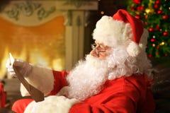 在家坐在他的室在圣诞树附近和读圣诞节信或愿望的愉快的圣诞老人画象 库存图片