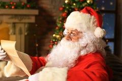在家坐在他的室在圣诞树附近和读圣诞节信或愿望的愉快的圣诞老人画象 库存照片