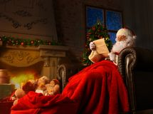 在家坐在他的室在圣诞树附近和读圣诞节信或愿望的愉快的圣诞老人画象 免版税库存图片