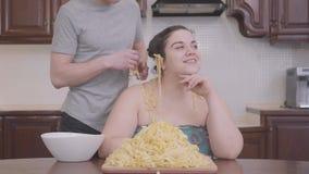 在家坐在厨房里的俏丽的肥满妇女 在他的肥胖女朋友的耳朵的亭亭玉立的白肤金发的人垂悬的面条 股票录像