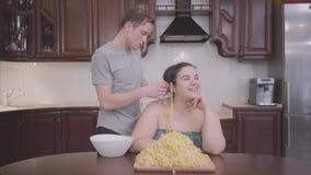 在家坐在厨房里的可爱的肥满妇女画象  在他的耳朵的亭亭玉立的白肤金发的人垂悬的面条 影视素材