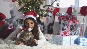 在家坐在圣诞树旁边的年轻俏丽的妇女画象戴着使用与缅因树狸猫的圣诞节帽子 影视素材