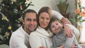 在家坐在圣诞树附近的快乐的家庭画象一起 儿童系列愉快的年轻人 影视素材