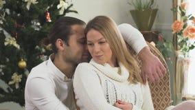 在家坐在圣诞树附近的愉快的夫妇画象  妻子和丈夫一起是愉快的 爱关系 股票录像