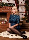 在家坐在壁炉冬天概念附近的年轻白肤金发的妇女 免版税库存图片