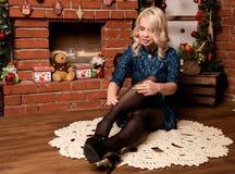 在家坐在壁炉冬天概念附近的年轻白肤金发的妇女 库存图片