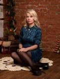 在家坐在壁炉冬天概念附近的年轻白肤金发的妇女 免版税库存照片