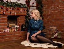 在家坐在壁炉冬天概念附近的年轻白肤金发的妇女 库存照片