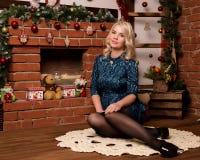 在家坐在壁炉冬天概念附近的年轻白肤金发的妇女 免版税图库摄影