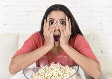 在家坐在客厅观看的电视可怕恐怖片的拉丁妇女沙发长沙发 库存图片