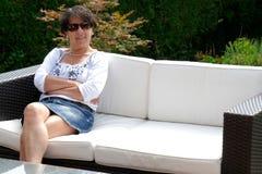 在家坐在庭院里的微笑的中年妇女画象  免版税图库摄影