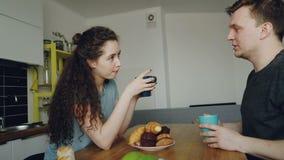 在家坐在桌上的年轻白种人夫妇在dicussing某事的现代厨房,卷曲妇女坐回到 股票录像
