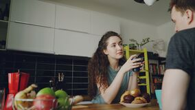 在家坐在桌上的年轻白种人夫妇在dicussing某事的现代厨房,卷曲妇女坐回到 影视素材