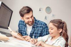 在家坐在桌人教学女孩的父亲和一点女儿愉快 库存照片