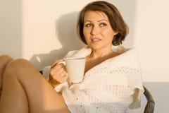 在家坐在羊毛被编织的毯子的椅子的成熟微笑的妇女有杯子的热的饮料,秋天冬天样式 免版税库存照片