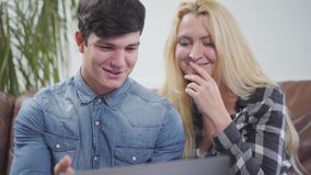 在家坐在膝上型计算机前面的可爱的夫妇 谈论一名深色的男人和白肤金发的妇女的画象项目 股票视频
