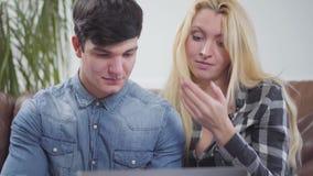 在家坐在膝上型计算机前面的逗人喜爱的夫妇 谈论一名深色的男人和白肤金发的妇女的画象项目  影视素材