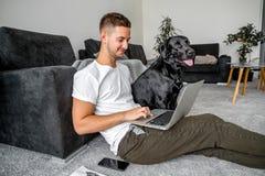 在家坐在膝上型计算机和与狗一起使用的自由职业者人 库存照片