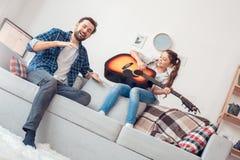 在家坐女孩的父亲和一点女儿唱歌与快乐的父亲 库存照片