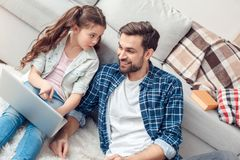 在家坐女孩的父亲和一点女儿指向惊奇的膝上型计算机 免版税图库摄影