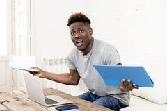 在家坐客厅的非裔美国人的人与便携式计算机和文书工作一起使用 免版税图库摄影
