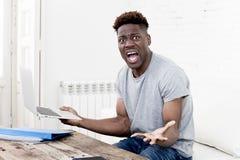 在家坐客厅的非裔美国人的人与便携式计算机和文书工作一起使用 免版税库存照片