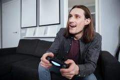 在家坐愉快的人的游戏玩家户内和戏剧比赛 免版税库存照片
