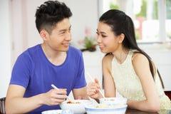 在家坐新中国的夫妇吃膳食 免版税库存图片