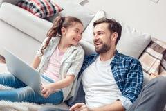 在家坐有膝上型计算机的父亲和一点女儿女孩看快乐的父亲 免版税库存照片