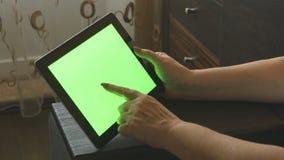 在家坐沙发和使用有绿色屏幕的,后面看法的年长妇女一台数字式片剂个人计算机 在成人的片剂个人计算机 股票录像