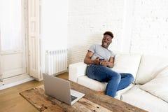 在家坐沙发长沙发的黑人与便携式计算机和手机一起使用 免版税库存照片